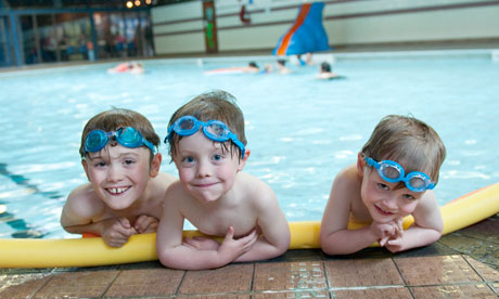 3 boys with goggles on top of head at the edge of the swimming pool
