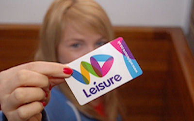 Woman holding a Passport to Leisure card - WDL logo on the card