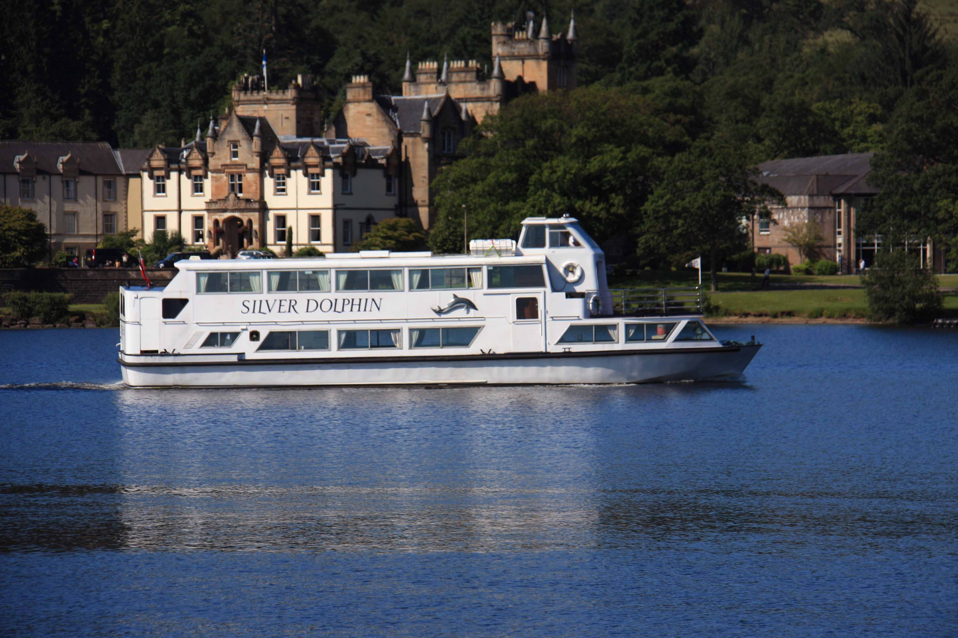 Sweeney's Cruises - Sliver Dolphin cruiser sailing past Cameron House