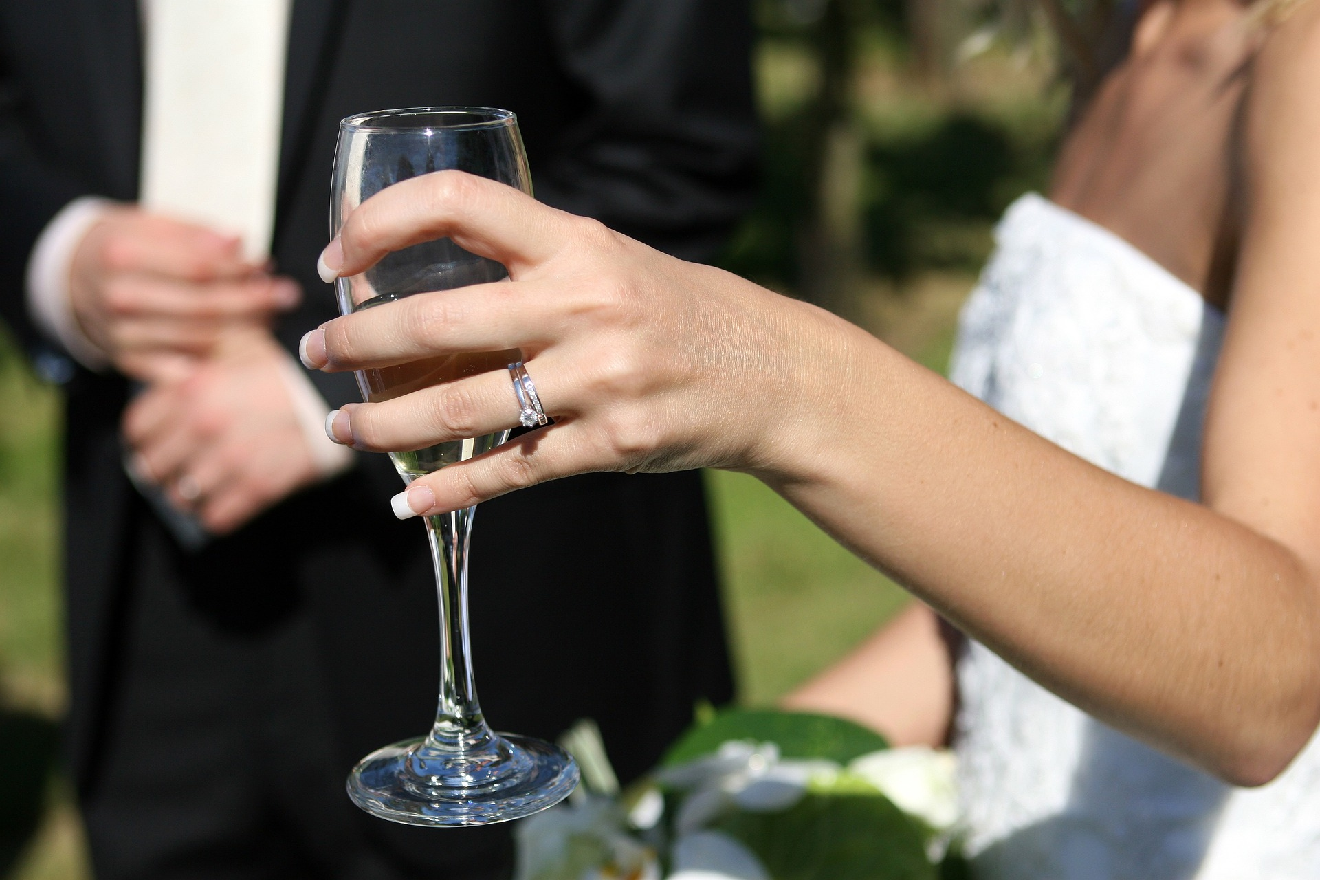 Bride holding a flute in her hand with wedding and engagement ring on show